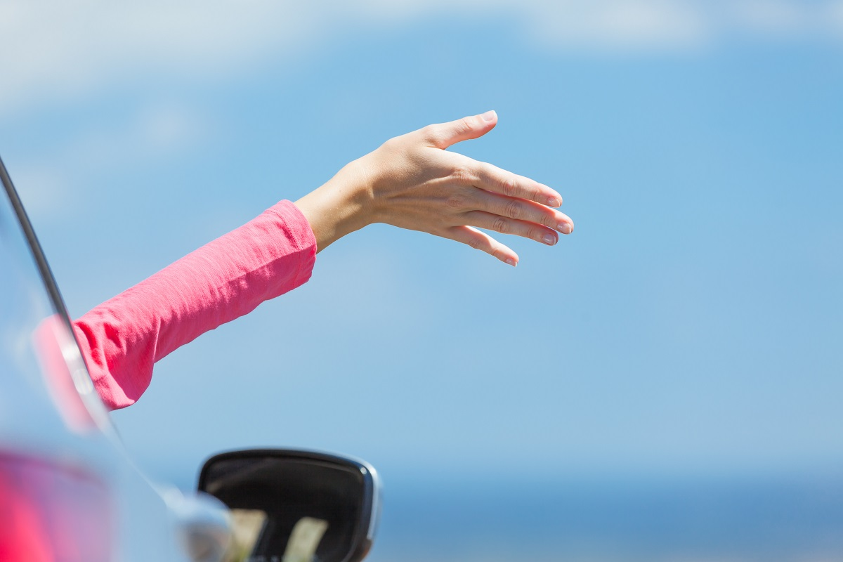 Freedom and travel concept. Happy woman traveling on the road with her hand out of the car feeling the breez.
