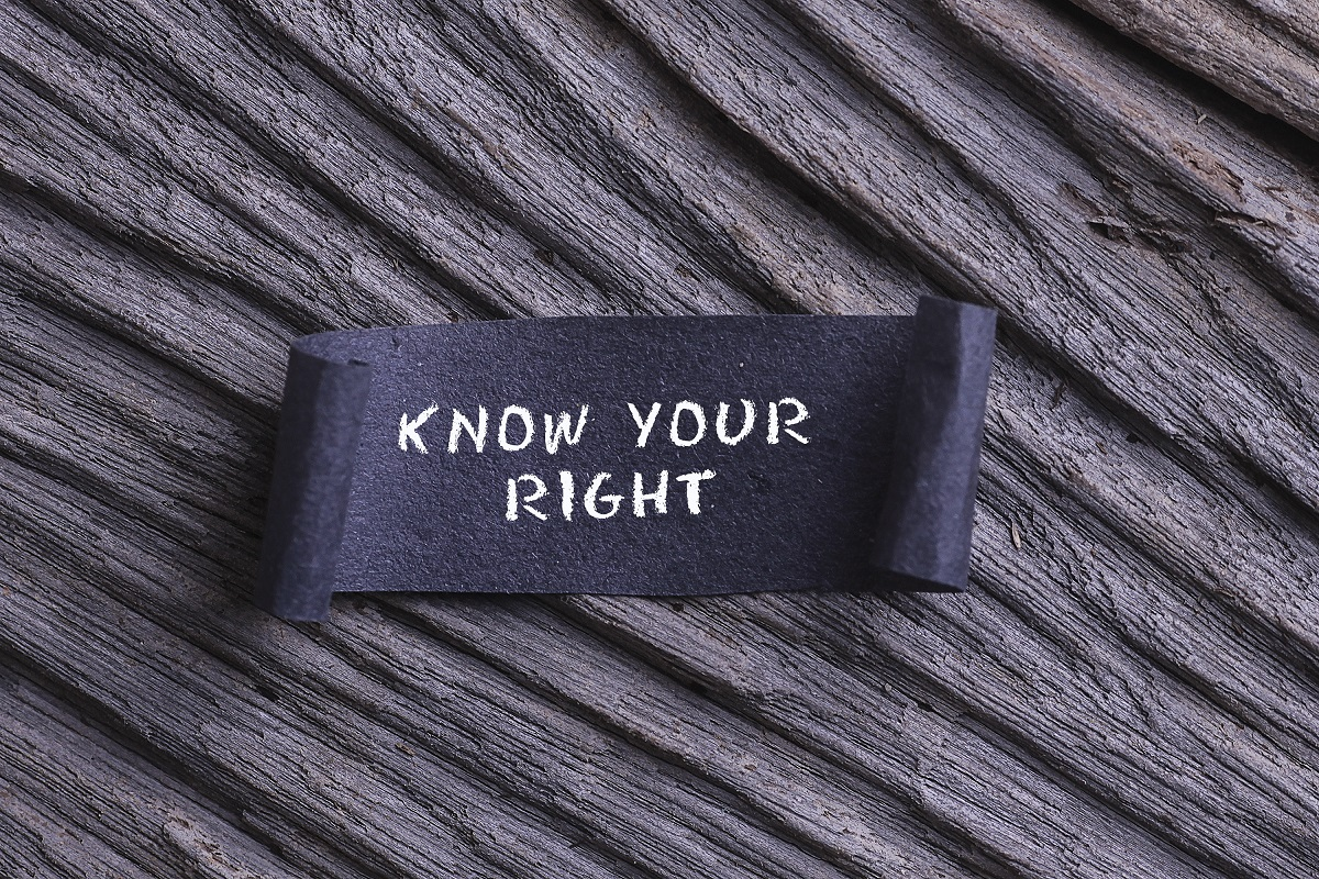 KNOW YOUR RIGHT word written on Black papper with wooden background