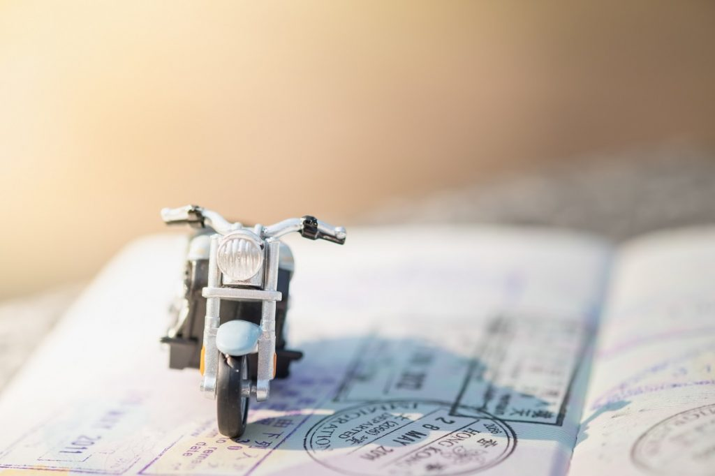 Travel Concept. Motorcycle miniature model figure on passport with immigration stamps under sunlight