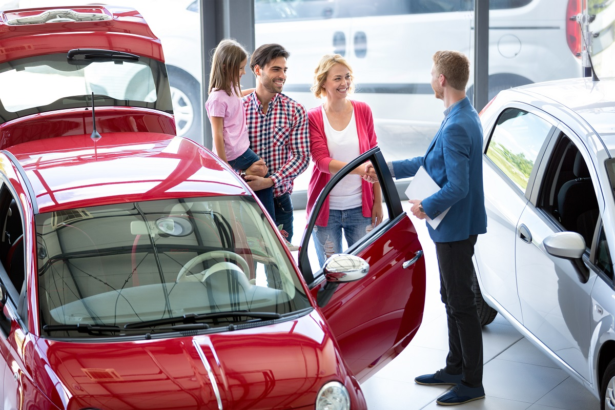 Smiling car agent showing vehicle to young family, all stand together next to the car in the car dealership saloon